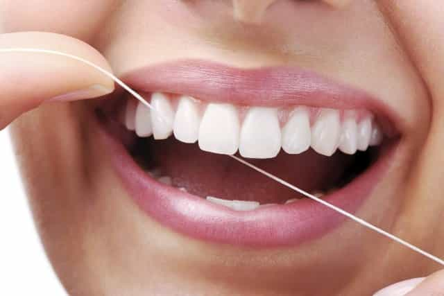 Brush and floss regularly to prevent white spots on teeth